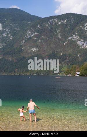Grand-père qui tient la main de son petit-enfant lors de l'entrée de l'eau froide du lac de Bohinj, plus grand lac permanent situé dans la vallée de Bohinj des Alpes Juliennes, parc national du Triglav, en Slovénie Banque D'Images