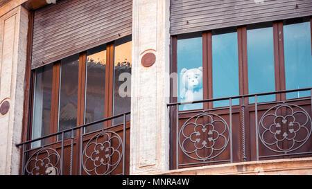 Un ours en peluche regarde par la fenêtre d'un immeuble Banque D'Images