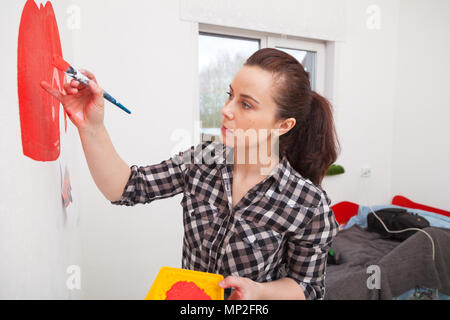 Jeune femme brune artiste en chemise à carreaux s'appuie sur un mur blanc d'une grande machine à écrire rouge dans une chambre du garçon. Maman dessiner une brosse avec la voiture de son fils. Banque D'Images