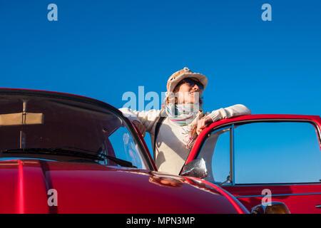 Femme 40s style hippie de profiter du beau temps en dehors de sa vieille voiture rouge. La vie et le style vintage, bleu clair le fond de ciel Banque D'Images