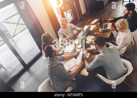 Vue du dessus de l'équipe de collègues assis à table en bois et travailler avec des documents et des appareils électroniques, ordinateurs portables. La diversité de démarrage d'équipe Banque D'Images