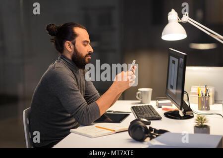 L'homme créatif avec le smartphone à l'office de nuit Banque D'Images