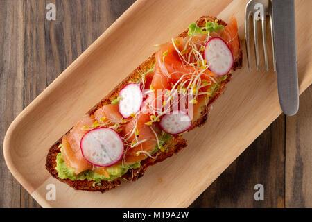 Toast de pain rustique avec la purée d'avocat, saumon fumé, radis, pousses de brocoli et servi dans une plaque de bois sur une table en bois rustique. Vue d'en haut Banque D'Images