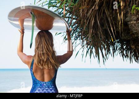 Fille sportive en bikini avec planche de surf à pied le long de la falaise la sombre. Jeune femme surfeur géré par plage de sable noir. Les personnes actives dans les sports adventure camp, e Banque D'Images