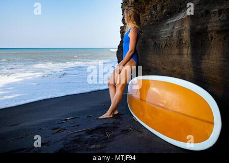 Girl in bikini with surfboard stand par cliff sur plage de sable noir. Femme Surfer en mer surf et vagues. Les personnes actives dans le sport aventure Banque D'Images