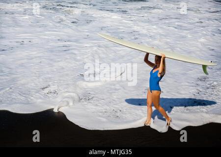 Fille sportive en bikini avec planche de surf à pied sur la plage de sable noir Jeune femme surfeur géré par eau douce avec mousse blanche. Les personnes actives dans le sport aventure Banque D'Images