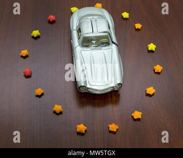 Vue de dessus de voiture jouet en forme de sucre dans les étoiles cercle. Banque D'Images
