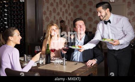 Poli smiling waiter apportant aux clients des plats commandés au restaurant Banque D'Images