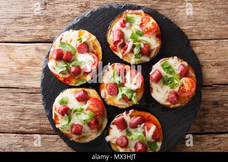 Aubergines au four de pizza avec de la mozzarella, tomates, saucisses et les verts gros plan sur la table. Haut horizontale Vue de dessus Banque D'Images