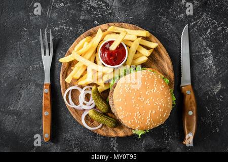 Burger de boeuf, frites, les cornichons, l'oignon et le ketchup. Vue de dessus de table. Concept de restauration rapide Banque D'Images