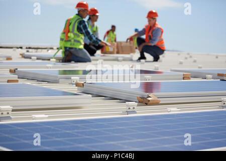 Les ingénieurs l'installation de panneaux solaires à sunny power plant Banque D'Images