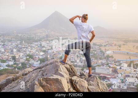 Photographe est debout sur le sommet d'une montagne à la recherche sur une ville du désert du Rajasthan avec des montagnes au loin. Banque D'Images