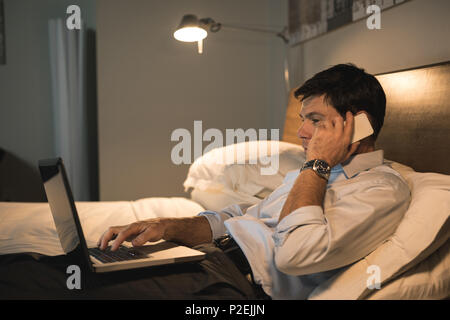 Businessman using laptop while talking on mobile phone Banque D'Images