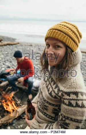 Portrait smiling woman, boire de la bière, en appréciant le surf week-end escapade au camping sur la plage de robuste Banque D'Images