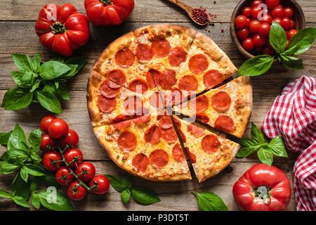 Pizza au pepperoni, tomates et basilic. Pizza au pepperoni savoureux sur fond de bois rustique. Vue de dessus de la pizza italienne Banque D'Images