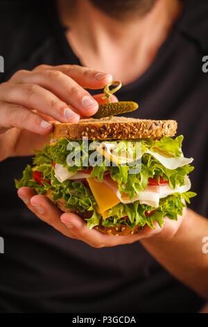 Big sandwich avec du pain, de la viande (porshutto), du fromage et des légumes frais dans les mains des hommes, un arrière-plan sombre. Banque D'Images