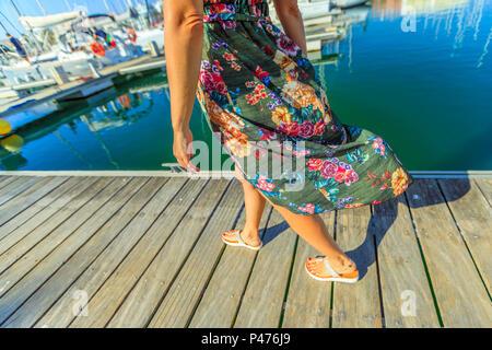 Détail de jambes de femme marche sur la jetée en bois de marina de Lagos sur la côte de l'Algarve, Portugal, Europe. Style de femme à la baie de Lagos en vacances d'été. Banque D'Images