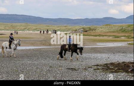 Les cavaliers d'une école d'équitation à Dunfanaghy Comté de Donegal en Irlande, sur une plage de sable de Sheephaven Bay. Banque D'Images