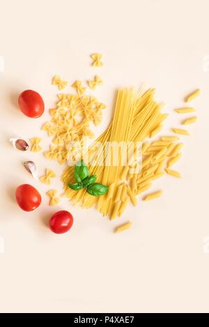 Diverses pâtes crues non cuites avec du basilic, tomates et l'ail rose sur fond pastel. Les pâtes italiennes: penne, farfalle, spaghetti. Banque D'Images