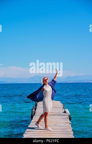 Jeune femme heureuse sur le pont, près de la mer, l'heure d'été, en toute sécurité avec une assurance vacances. Copie espace.belle femme en robe blanche marche, danse sur la jetée en bois Banque D'Images