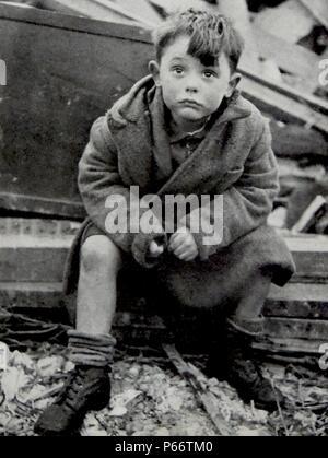 Un enfant orphelin a l'air choqué après avoir survécu au blitz sur Londres, par des fusées allemandes V2 1944 Banque D'Images