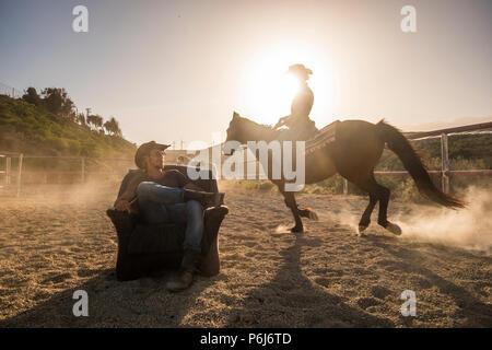 Les cavaliers avec les chevaux dans le coucher du soleil doré de lumière. Un homme assis sur un vieux fauteuil et une femme ride autour de lui rendre la poussière. image paysage avec moulins à vent dans la région de b Banque D'Images