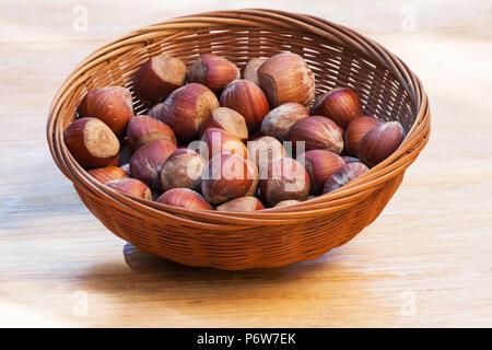 Les noisettes dans un panier sur une table en bois Banque D'Images