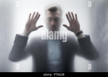 Silhouette d'upset businessman toucher les yeux fermés, les mains derrière le verre à vitre Banque D'Images