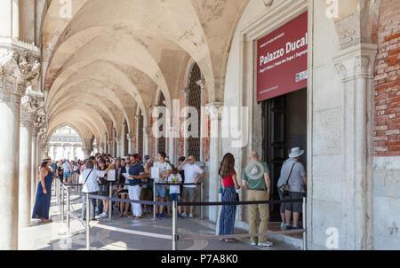 Longue file d'attente de touristes d'entrer dans le Palais des Doges, Le Palais Ducale, Palais Ducal à San Marco, Venise, Vénétie, Italie queuing sous l'arcade o Banque D'Images