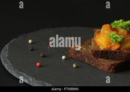 Les canapés d'un Ragoût végétarien (ragoût) sur un morceau de pain sur un fond noir Banque D'Images