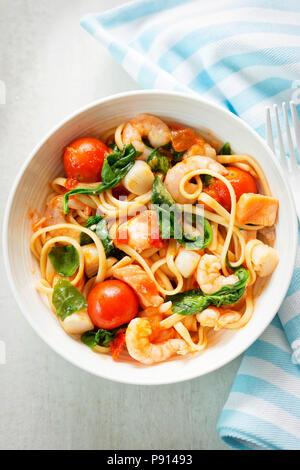 Linguine aux fruits de mer crevettes, pétoncles et saumon, Épinards et tomates Banque D'Images