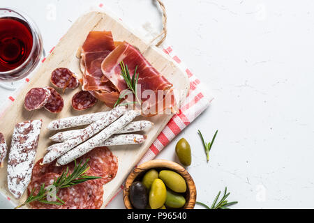 Antipasti italiens traditionnels, viandes tranchées ensemble avec le vin et les olives sur la table blanche. Vue de dessus, copiez l'espace. Banque D'Images