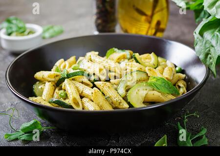 Pâtes penne au pesto, courgettes, pois verts et basilic. Cuisine italienne. Banque D'Images