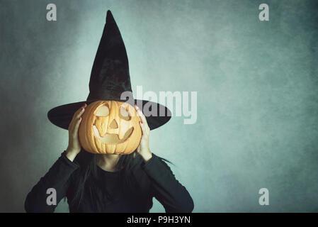 Jeune femme tenant une citrouille à l'halloween Banque D'Images