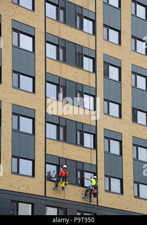 Deux laveurs de vitres de la descente en rappel d'utilisation de cordes pour accéder à Windows sur une nouvelle forme de tour dans le centre-ville de Portsmouth, Hampshire, Royaume-Uni Banque D'Images