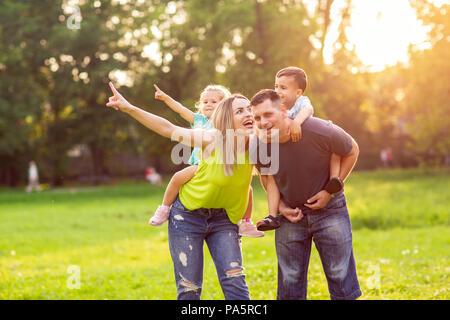 Drôle de jeunes parents Donner aux enfants piggyback ride in park Banque D'Images