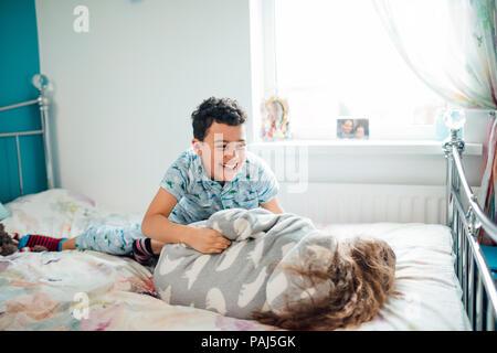 Petit garçon et sa grande sœur sont playfighting sur un lit à la maison. Banque D'Images