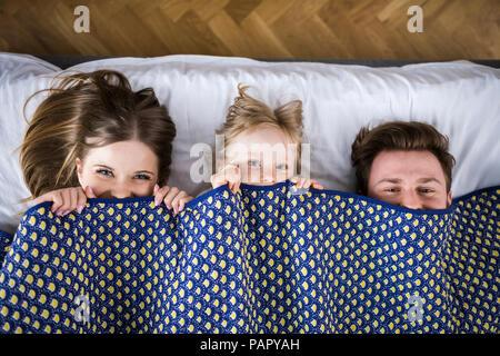 Famille heureuse au lit, se cachant sous couverture Banque D'Images
