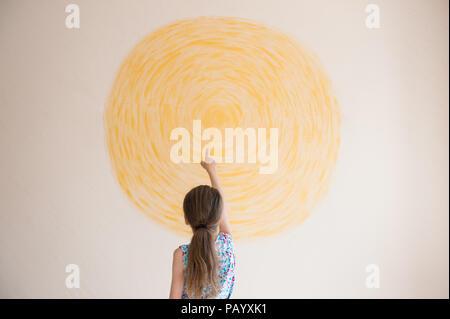 Petite fille face au soleil jaune peint sur mur intérieur Banque D'Images
