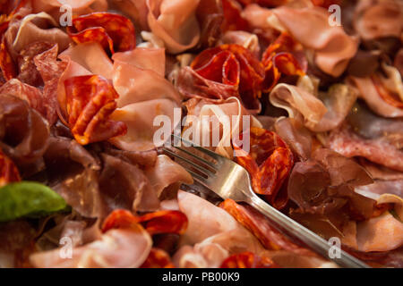 Close up de différents types de viande (jambon italien) sur une assiette avec une fourchette et une feuille de basilic Banque D'Images