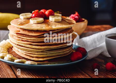 Crêpes maison avec des fruits. Tranches de bananes et de fraises congelées. Banque D'Images