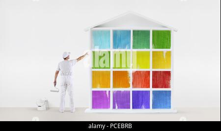 Vue arrière du peintre homme pointant avec le doigt les couleurs chambre modèle sur mur, avec rouleau à peindre et de godet, isolated on white Banque D'Images