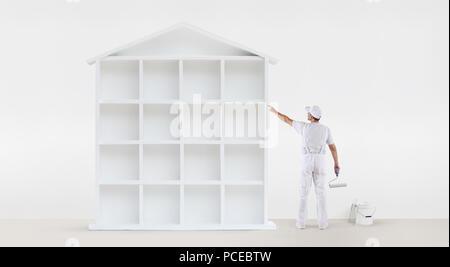 Vue arrière du peintre homme pointant du doigt avec le modèle de la maison blanche sur mur, avec rouleau à peindre et de godet, isolé sur fond blanc Banque D'Images