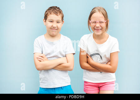 Enfants frère et soeur jumeaux de 8 ans debout avec grimaces sur fond bleu Banque D'Images