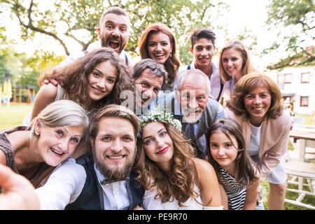 Mariée, marié avec vous en tenant à l'extérieur de réception de mariage selfies dans l'arrière-cour. Banque D'Images