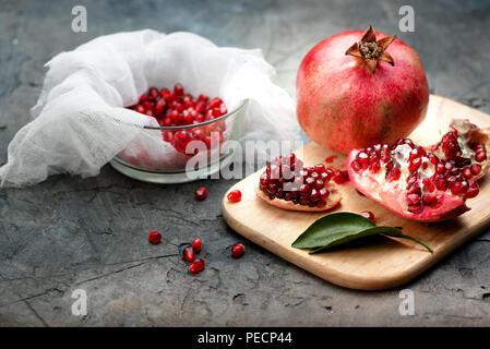 Fruits de Grenade avec des grains et des feuilles sur la table. Faire du jus. Banque D'Images