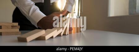Vaste panorama d'un homme d'arrêter l'effet domino en insérant sa main dans une ligne de blocs qui tombent avec un brillant sunburst de derrière. Banque D'Images