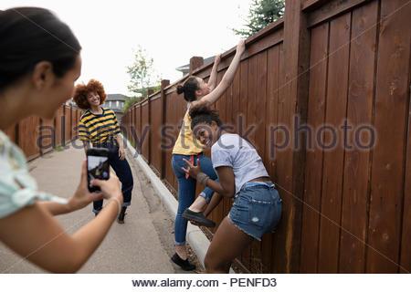 Teenage girl friends ludique avec téléphone appareil photo grimpe sur la clôture Banque D'Images