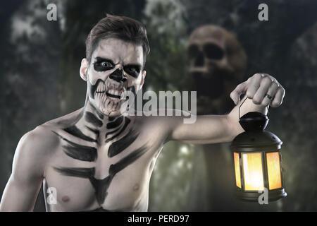 L'homme à l'imperméable provenant de forêt sombre avec lanterne rougeoyante dans sa main concept. Silhouette d'un tueur d'horreur avec lampe. Banque D'Images
