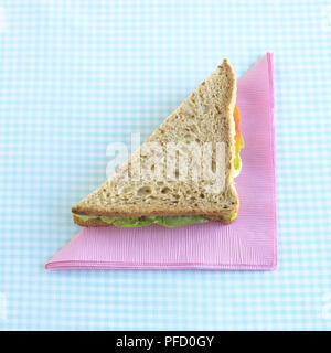 Sandwich au fromage et salade coupé en forme triangulaire sur serviette rose à carreaux bleus sur le tapis de table. Banque D'Images